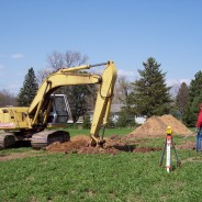 Another view of the backhoe breaking ground for the Shrine.