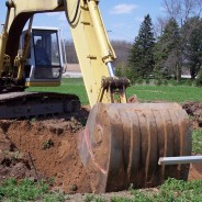 A backhoe breaking the ground where the future Shrine will be.