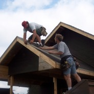 Photo of workers nailing tarpaper on new roof.